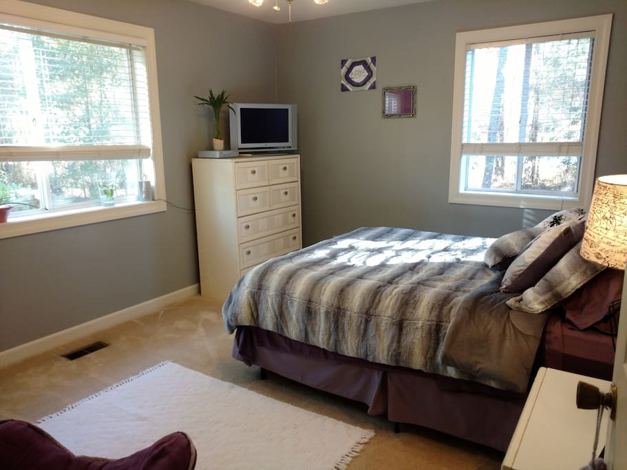 Main Guest Bedroom. Queen bed, night stand, dresser, large windows overlooking secluded, wooded setting