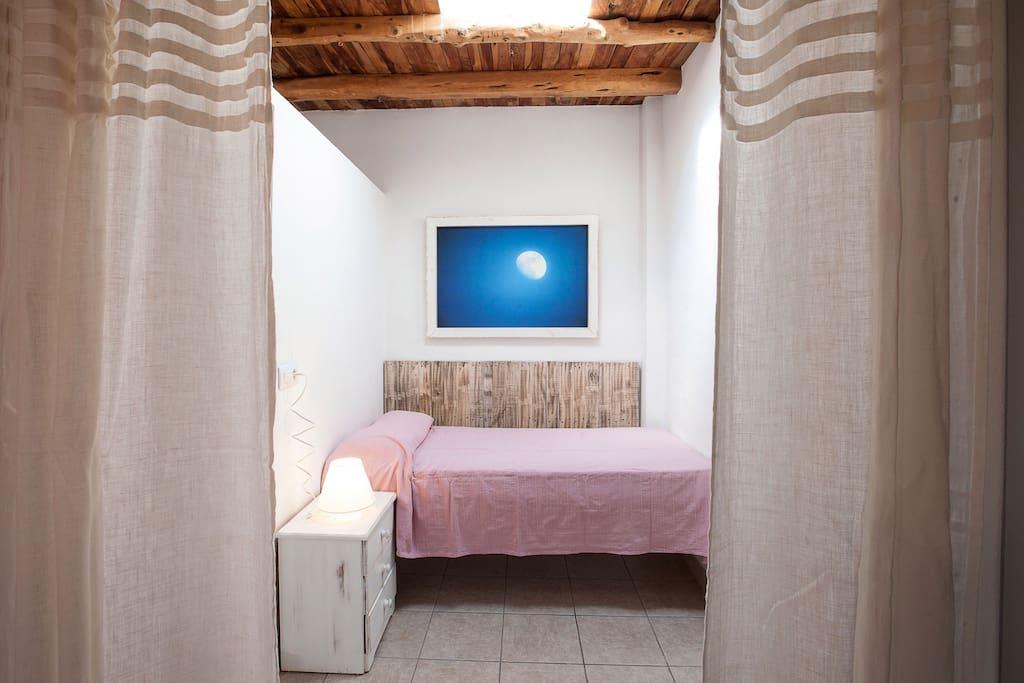 Cama individual. La habitación comunica con la de matrimonio y esta separada de ella por una cortina