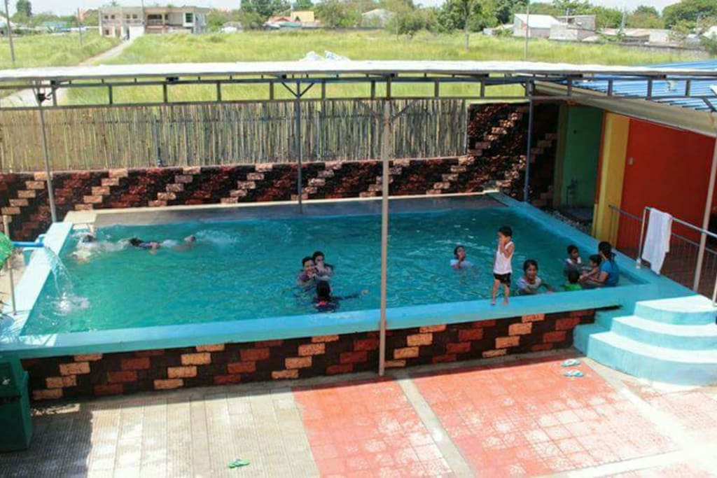 Swimming pool facility infront of 2-storey building (rooms)