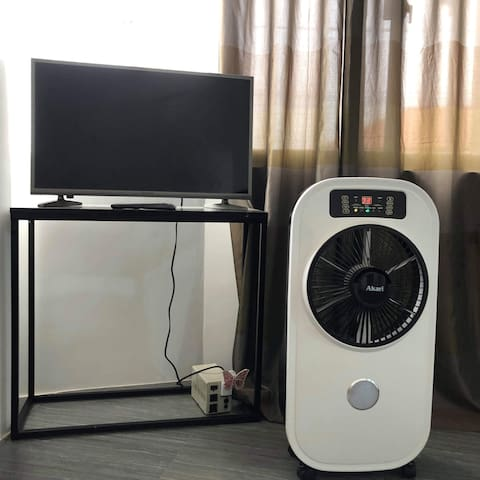 """Bedroom is furnished with a 32"""" SMART LED TV with TV Plus and a Rechargeable Mist Fan."""
