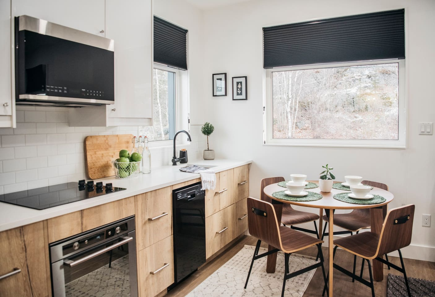 The modern kitchen has quartz counter tops, a stove top, a wall oven, a microwave and a dish washer.  The large windows make the kitchen bright and you can view the surrounding area while cooking!