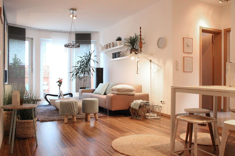 65m2 mit großer Süd Terasse. Wohnzimmer, hell modern eingerichtet, mit Kuschelkissen und Kuscheldecke.