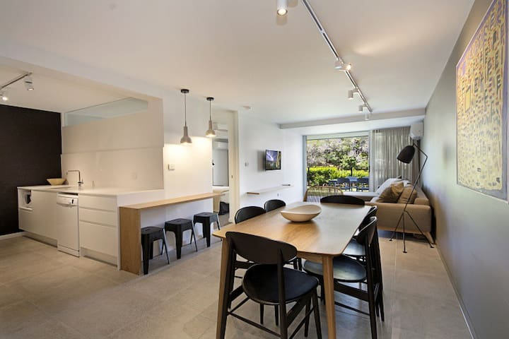 ground floor river view apartment with full size kitchen, dining and lounge opening up to manicured lawn and Noosa River views