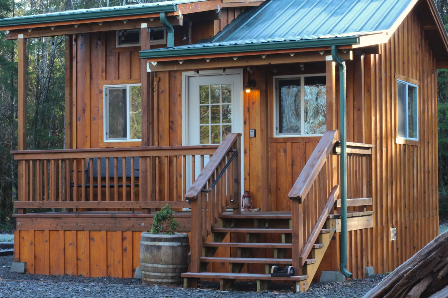 Cabin includes covered seating area with string lights, a hand rail and boot brush to clean off dirt before entering cabin.