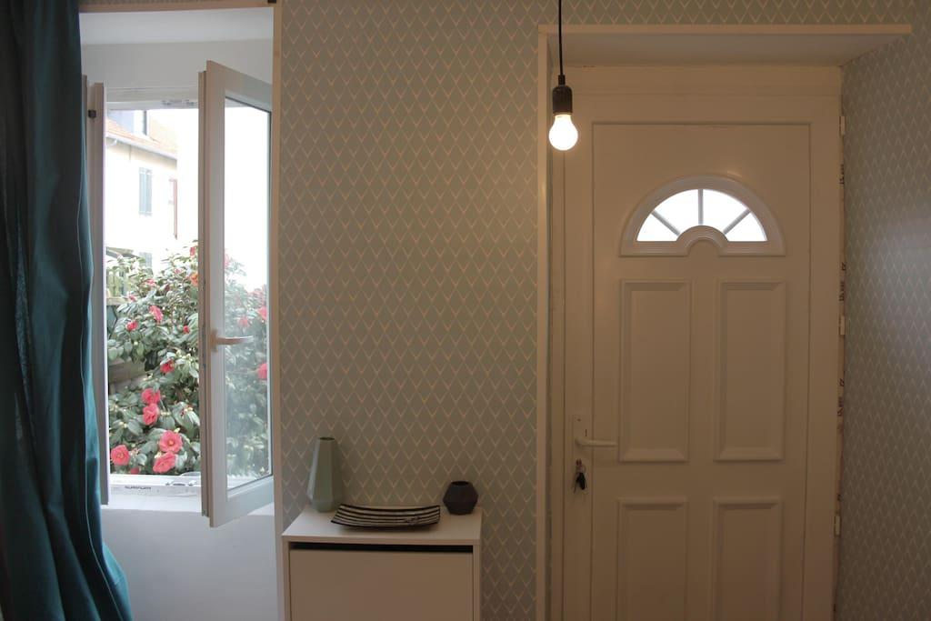 Porte d'entrée et fenetre donnant dans le salon.