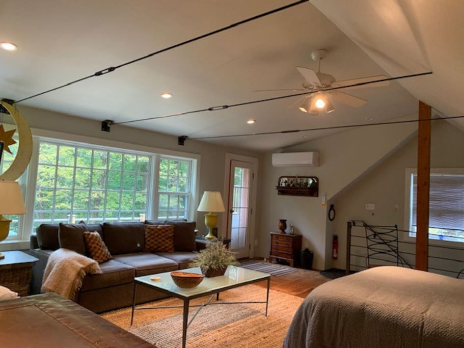 A warm natural wood floor studio space greets you as you enter. Stained glass and copper accents. Two beds (queen bed and extra firm king sleeper couch) are available. Perfect for two people, a bit tight (but possible)  for three or four guests.