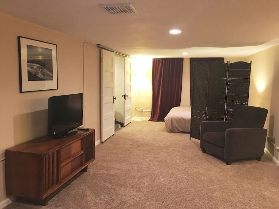 Another photo of the living space with the room divider and the extra bed on the other side.