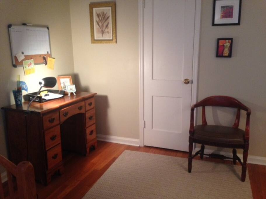 Room has desk, as well as a closet for storing clothes.