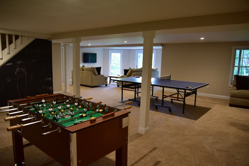 Walk out basement game-room with TV and two seating areas