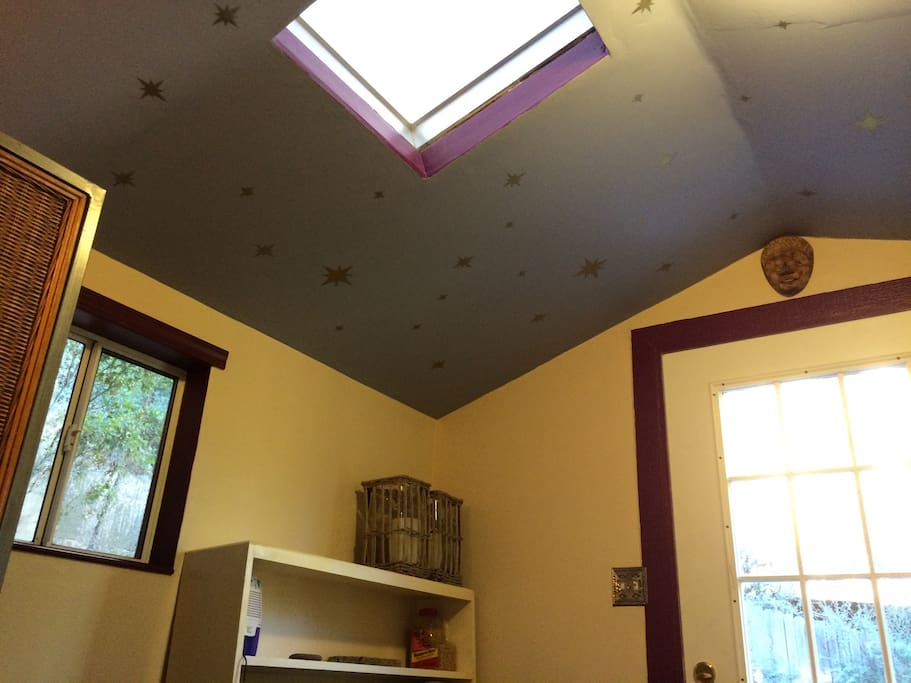 Star painted ceiling. On the left is the window facing uphill, and on the right is the window in the door. Above is skylight.