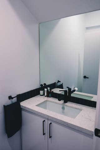 Your private ensuite with stone-top vanity and modern rimless toilet.
