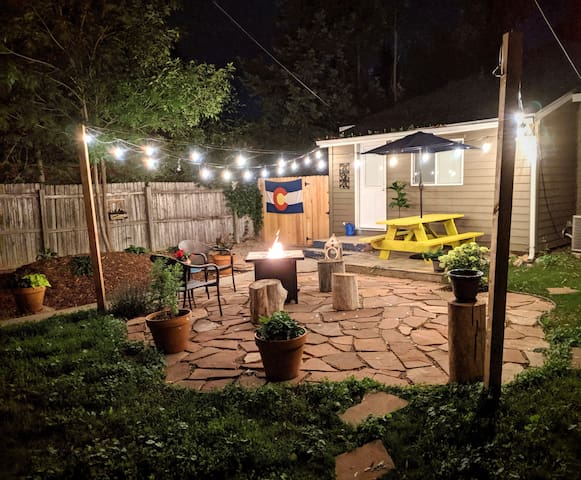 Patio area at night complete with firepit,   outdoor lighting, and plenty of seating