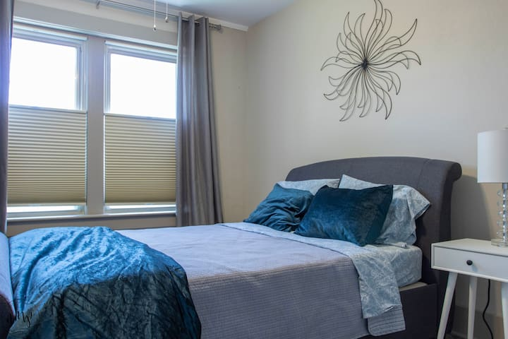 Queen sized bed with large windows for natural light