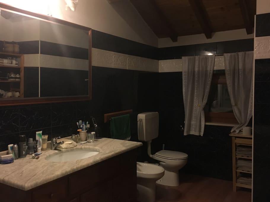 Elegante e spazioso Bagno in marmo blu e parquet. Elegant bathroom in blue marble.