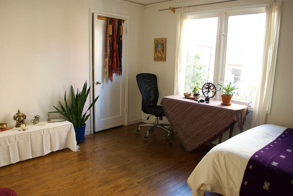 Bedroom has hardwood floors, a table/desk with an office chair, happy plants, artwork and ample open space to stretch or practice yoga.