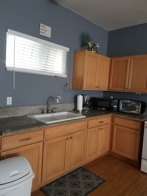 Kitchenette with appliances and granite counter tops.
