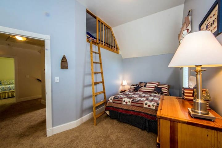 One of the upstairs rooms features a queen bed and loft with a small single bed.