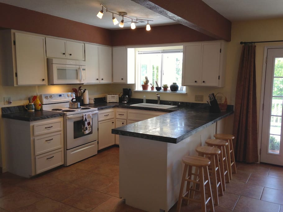 Kitchen is fully equipped and has custom cabinets, slate countertops and tile floors