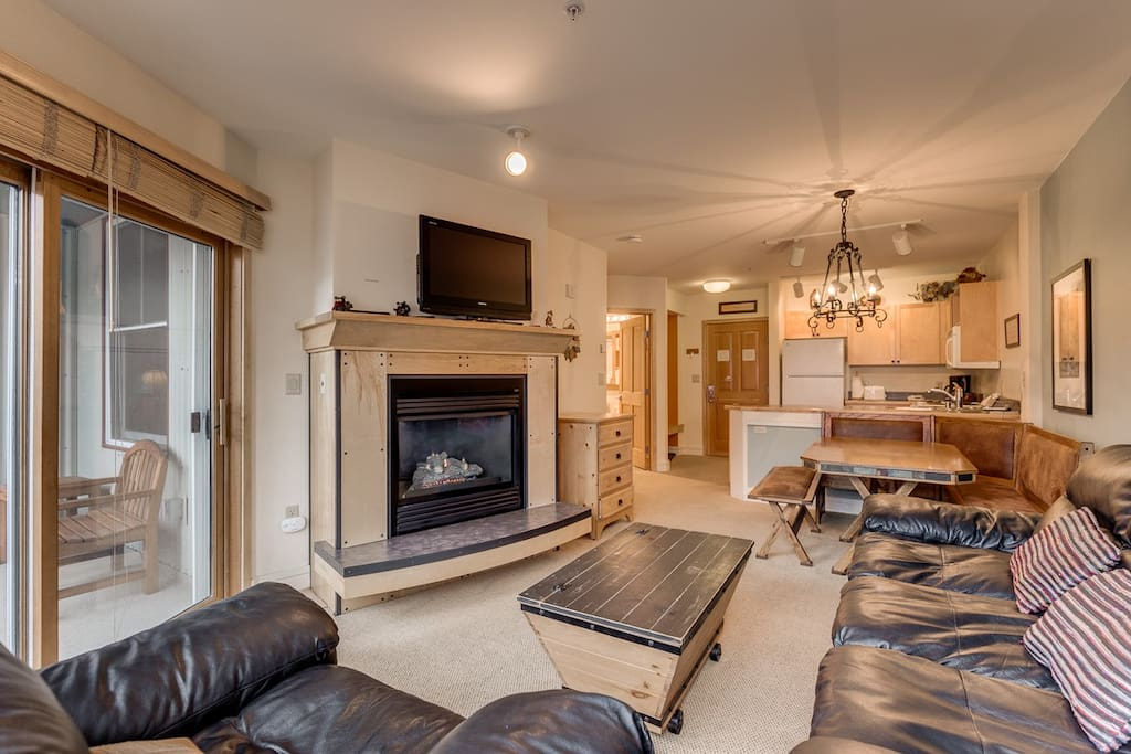 The living area features a flat screen TV above a beautiful gas fireplace and a queen-sized sleeper sofa.