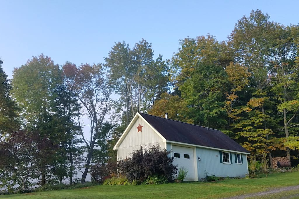 Front view of cottage and garage entry from driveway during early fall.