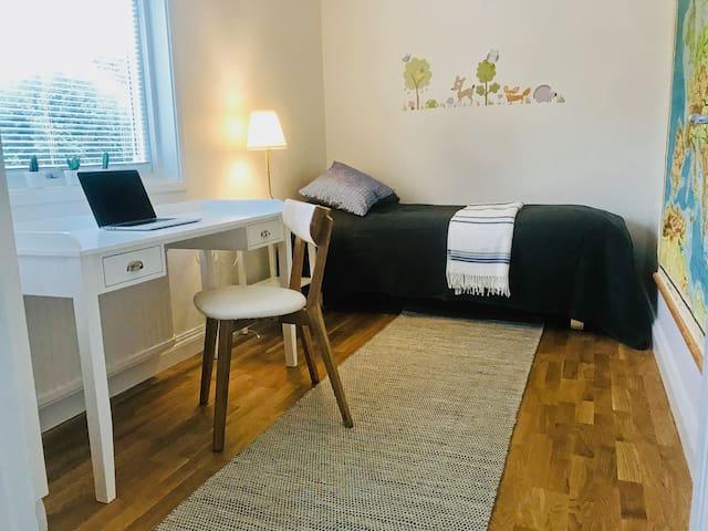 Ett av de två mindre sovrummen med enkelsäng och ett skrivbord / One of the two smaller bedrooms with a single bed and a writing desk