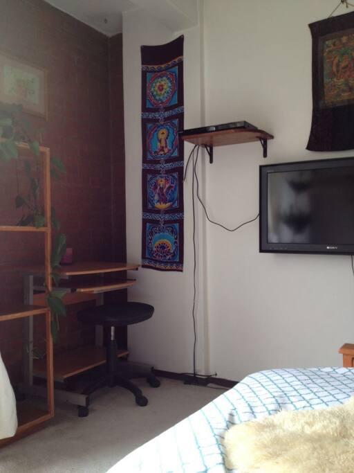 Television con cable y  mueble para lap top.
