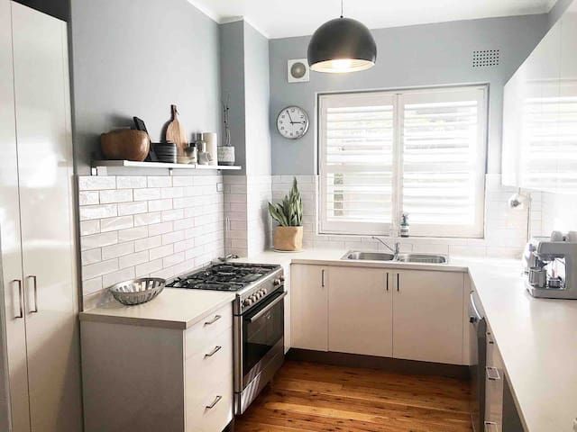 Fully equipped, eat-in kitchen with modern stainless steel appliances and a  Breville coffee machine