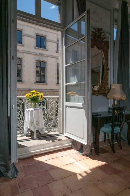 Romantic decor on a French balcony of an apartment with terracotta tile and French doors. Versailles style furnishings and luxurious architecture paint a picture of South of France charm. #france #apartment #french #Paris #balcony