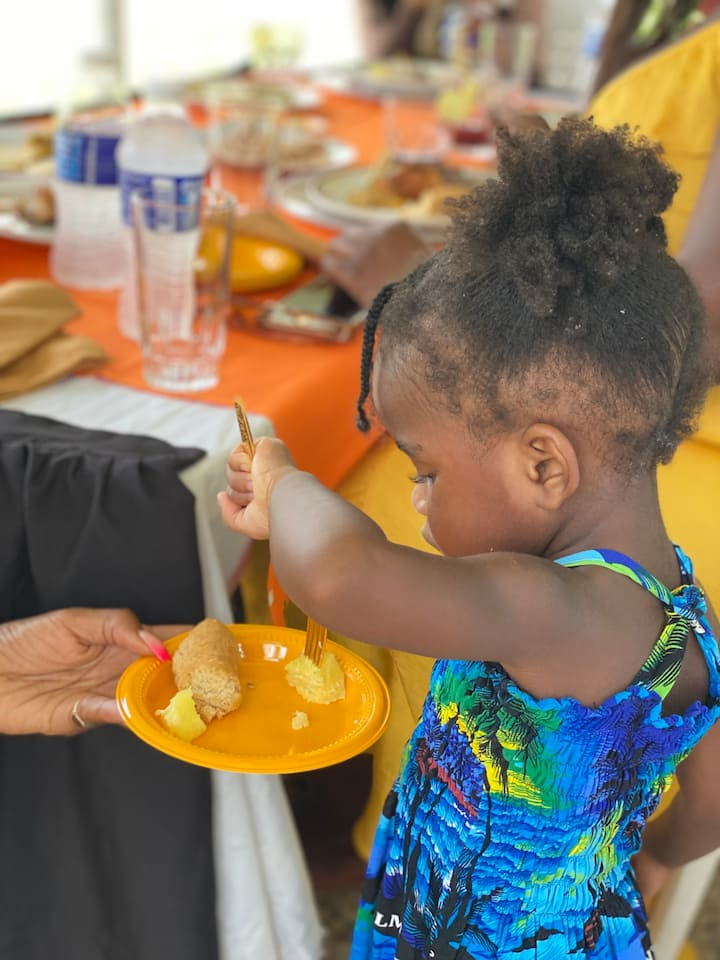 Baby girl eating yellow yam