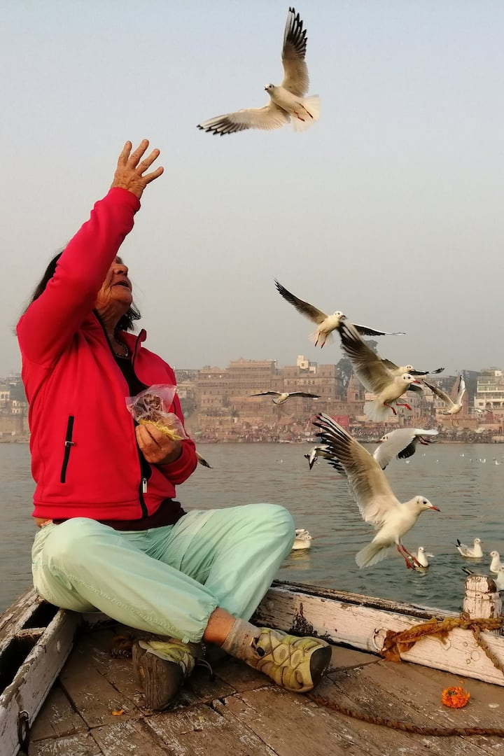 Feeding the birds on holy river Ganga