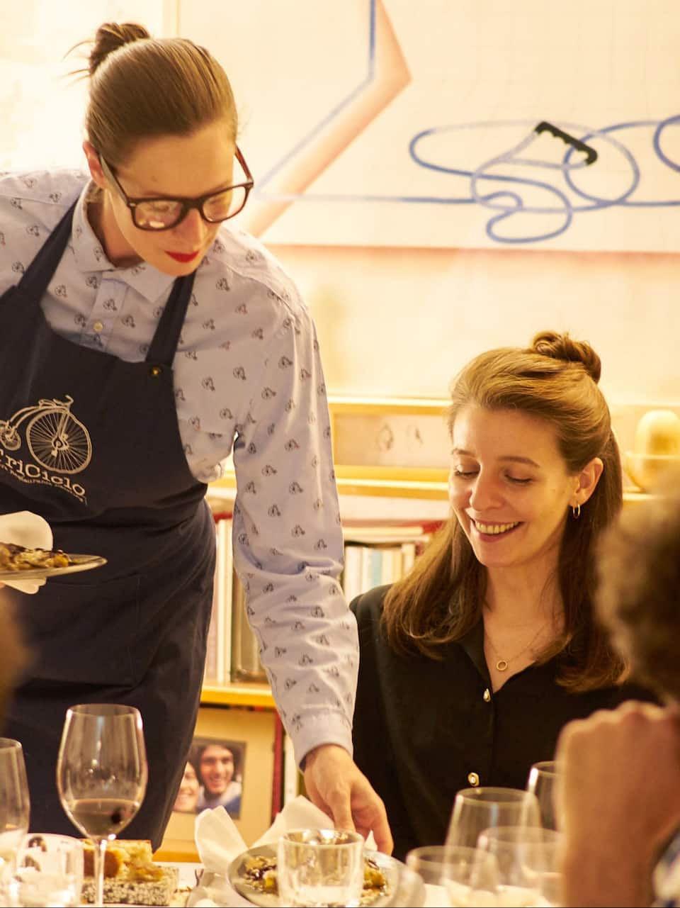 Woman being served a gourmet meal by chef