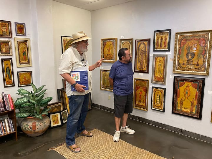 Guide Sam Richardson describing antique Spanish icons and retablos at a local gallery.