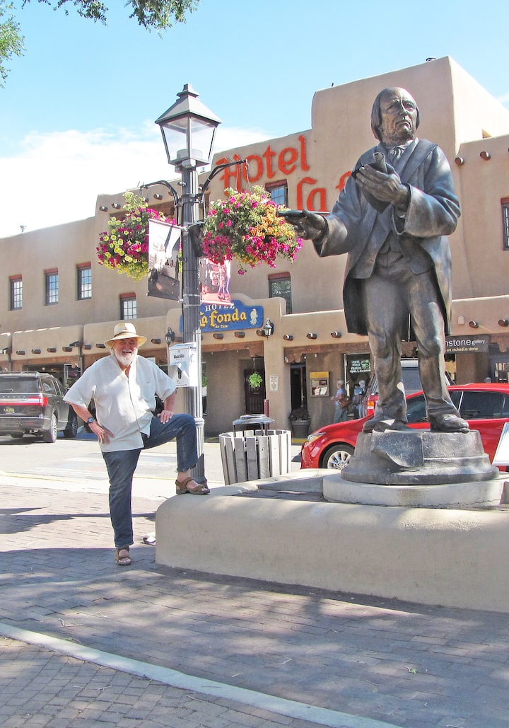 Taos Walking Tours guide and owner Sam Richardson waiting to meet a group at the Taos Plaza. The statue is Padre Martinez, known as the Ben Franklin of New Mexico. He brought the first printing press and started the first newspaper.