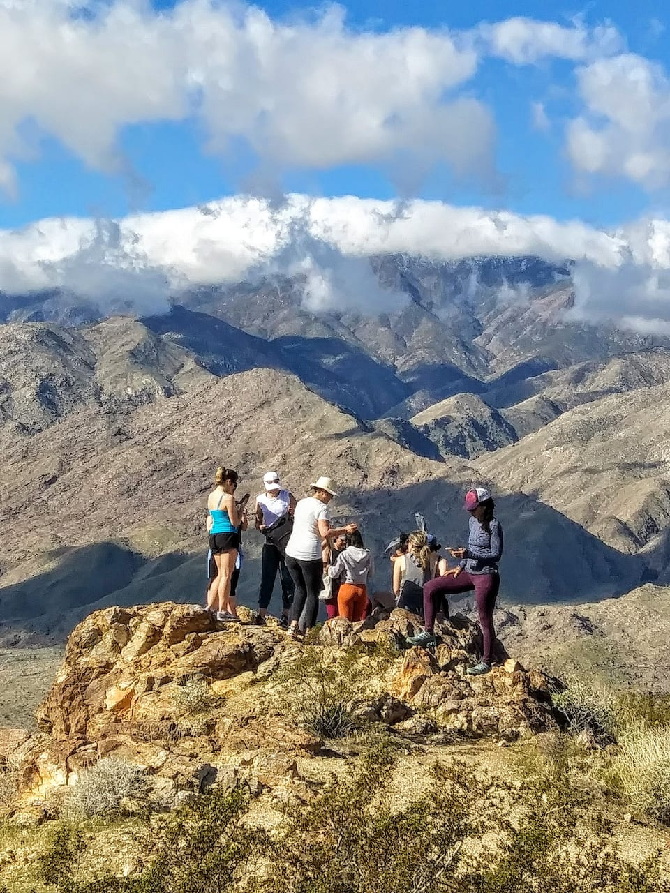 Group of hikers atop a peak in desert mountains