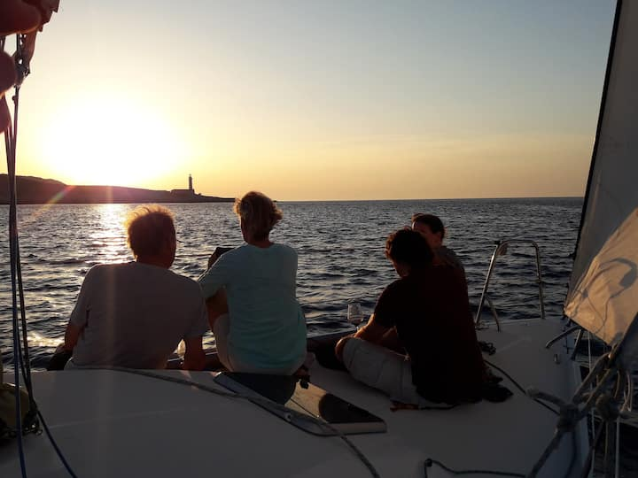 Sailing to lighthouse at sunset