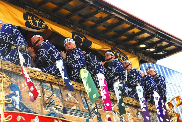 Flute players ride atop the shrines
