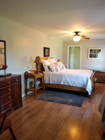 Large, bright master bedroom, with ensuite through doorway. Clean linens from the ripple coverlet to the mattress pad, which is what we would expect.Reading lamps on both sides, drawers and walk in closet for you items.