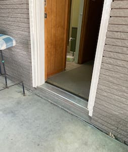 """This shows our entryway.  It is located in a carport. You can park a few steps away from this door for further accessibility. The step up is 4 1/2 inches but we have a moveable ramp. Inside, it entirely flat with no steps. Entryway is 29"""" wide."""