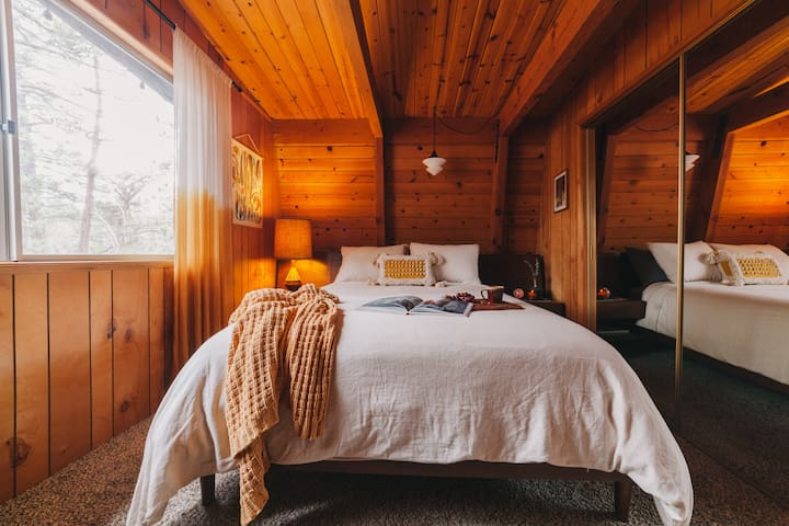 The back bedroom has a queen bed with built in headboard and nightstands. The window overlooks the forest out back. The sliding, mirrored closet has plenty of room to hang clothes.