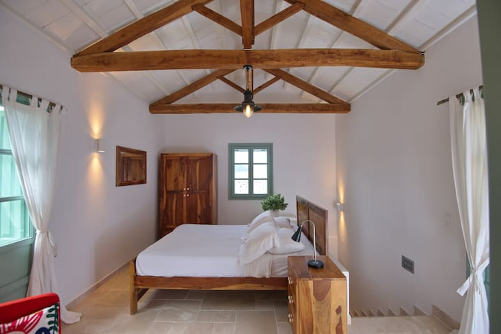 Double room on the upper area via an enclosed staircase from the living room .Leads onto outside upper terrace with seating and has its own balcony with country side view . ensuite , airconditioned and mosquito nets on the window shown