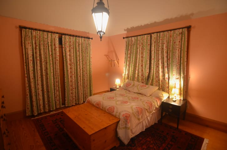 The bedroom on the third floor has a full bed, vaulted ceiling, and private balcony.