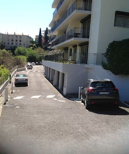 White car on left is parked outside level entrance hall and elevator