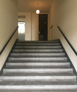 Please walk up the flight of stairs and in to corridor right of elevator