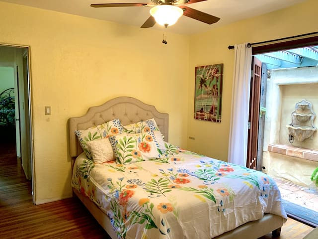 Bedroom with queen bed. French doors open to a small patio, fountain, and spa.