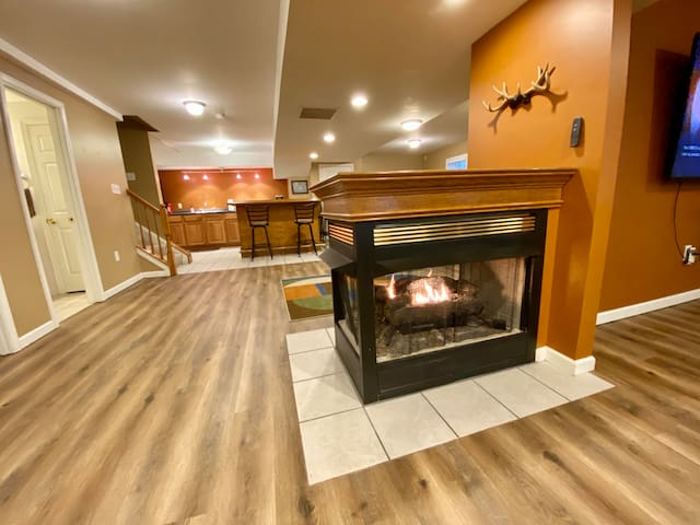 gas fireplace on lower level with second kitchen area in the background