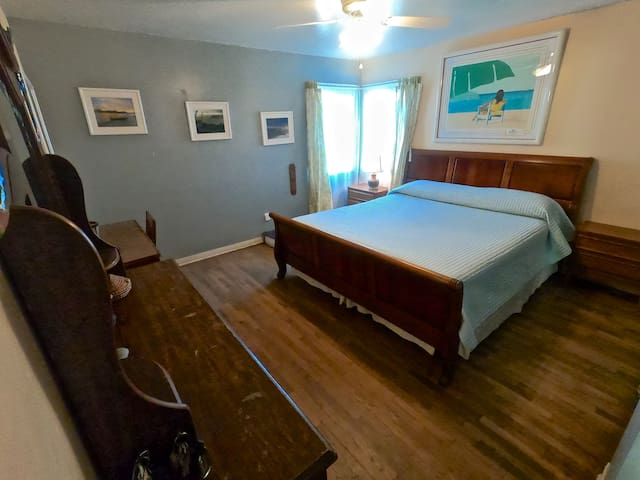 The master bedroom in Robert's Apartment. Has a chest of drawers, Computer Desk and California King Bed.