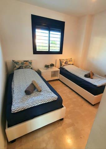 Vieras makuuhuoneessa on kaksi 190x90 kokoista sänkyä.