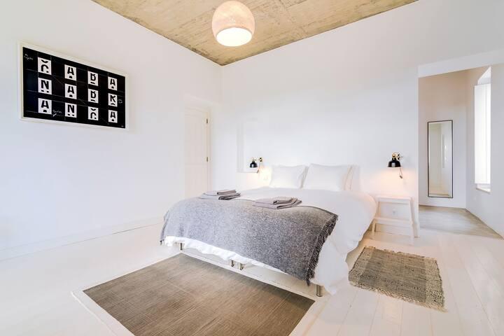 Chambre 1 au rez-de-chaussée. Avec son dressing attenant  et sa salle de bain. Lit double et plancher clair, fenêtre donnant sur une terrasse mignonne.