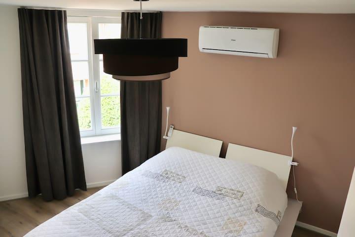 Slaapkamer met airco en heerlijk bed + verduisteringsgordijnen.