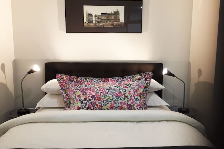 Hotel quality Queen bed with crisp luxurious bed linen.